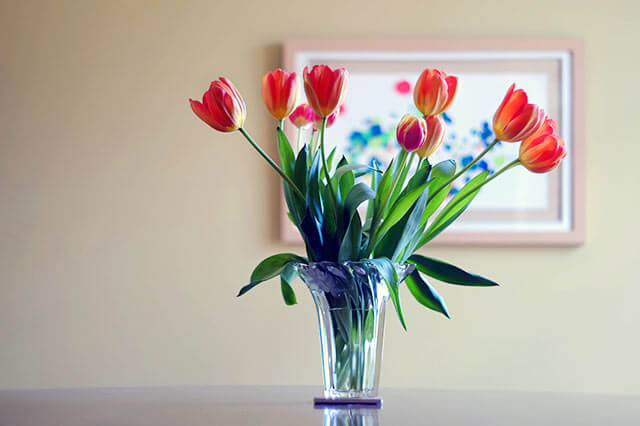 Vase with colorful tulips on a table.