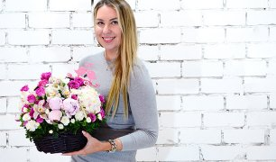 Smiling woman holding a basket of flowers