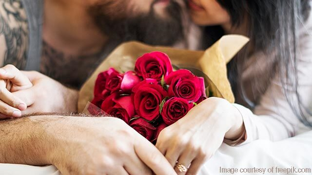 Man kissing and presenting roses to his sweetheart