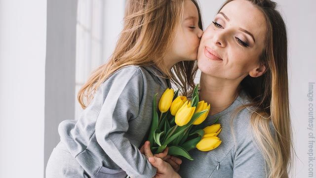 Young shild presenting flowers to her Mother