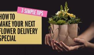 Hands holding a flower arrangement in a paper gift bag.